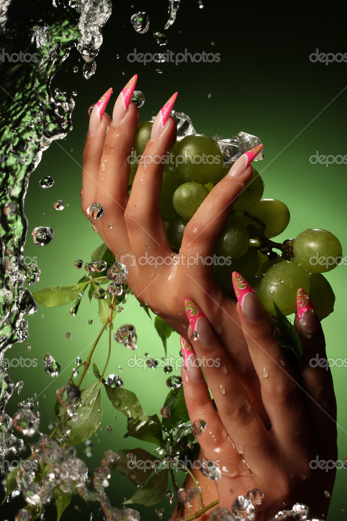 Hands of a young woman with a nice manicure.Оn a green background with grapes. — Stock Photo #3757601