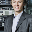 Portrait of young data center specialist in front of equipment — Stock Photo