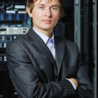Young businessman in hi-tech datacenter in front of equipment — Stock Photo