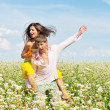 Young couple on field of flowers — Stock Photo