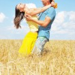 Young couple on wheat field — Stock Photo