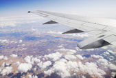 Airplane wing over colourful landscape — Stock Photo