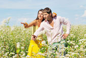 Young couple playing on field of flowers in sunny day — Stock Photo