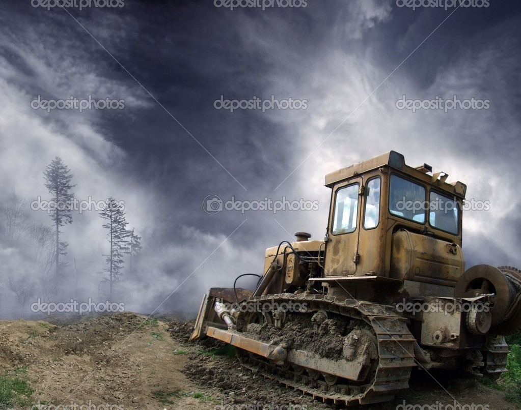 A picture of bulldozer standing in front of misty forest — Stock Photo #3761298