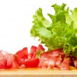 Sliced tomatoes and the fresh lettuce on the board - Stock Photo
