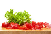 Sliced tomatoes and the fresh lettuce on the board — Stock Photo