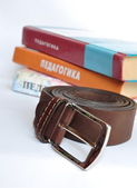Male leather belt on background pedagogical textbook — Stock Photo