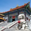 Lion statue in front of temple - Stock Photo