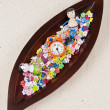 图库照片: Children doll in wooden leaf tray