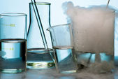 Laboratory glassware during experiment with vapor eruption — Stock Photo