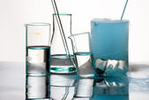 Laboratory glassware during experiment with blue vapors — Stock Photo