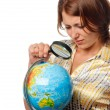 Girl attentively examines the globe through a magnifier — Stock Photo