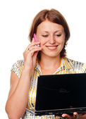 Girl with the laptop speaks by a mobile phone — Stock Photo