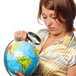 Girl attentively examines globe through magnifier — Stock Photo #3844301