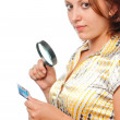 Girl considers a credit card through a magnifier — Stock Photo #3844381
