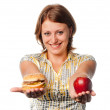 Smiling girl stretches apple and hamburger — Stock Photo