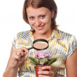 Smiling girl considers violets through a magnifier — Stock Photo