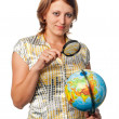 Girl examines the globe through a magnifier — Stock Photo