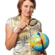 Girl examines the globe through a magnifier — Stock Photo #3849547