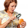 Surprised girl considers a hamburger through a magnifier — Stock Photo #3849565