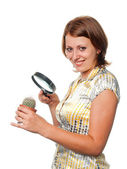 Smiling girl considers a cactus through a magnifier — Stock Photo