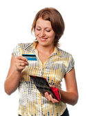 Smiling girl looks at a credit card — Stock Photo