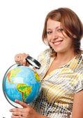 Smiling girl examines the globe through a magnifier — Stock Photo