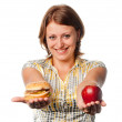 Stock Photo: Smiling girl stretches apple and hamburger