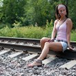 Slim lady is sitting on a railroad - Stock Photo