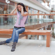 Cute brunette on  bench over mall background - Stock Photo