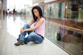 Smiling girl is sitting in the shopping mall — Stock Photo