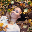 Smiling girl laying on leafs - Stock Photo