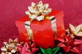 赤いクリスマス ギフト ボックス ゴールド リボン カラフルな弓 — ストック写真