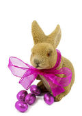 Easter bunnie with pink bow and Easter eggs. — Stock Photo