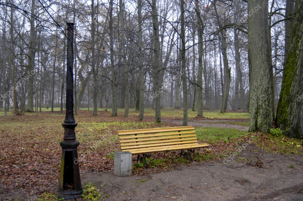 Yellow wooden bench and broken lamppost in empty park in autumn                                 — Stock Photo #3903548