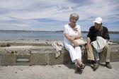 äldre par som sitter på väggen — Stockfoto