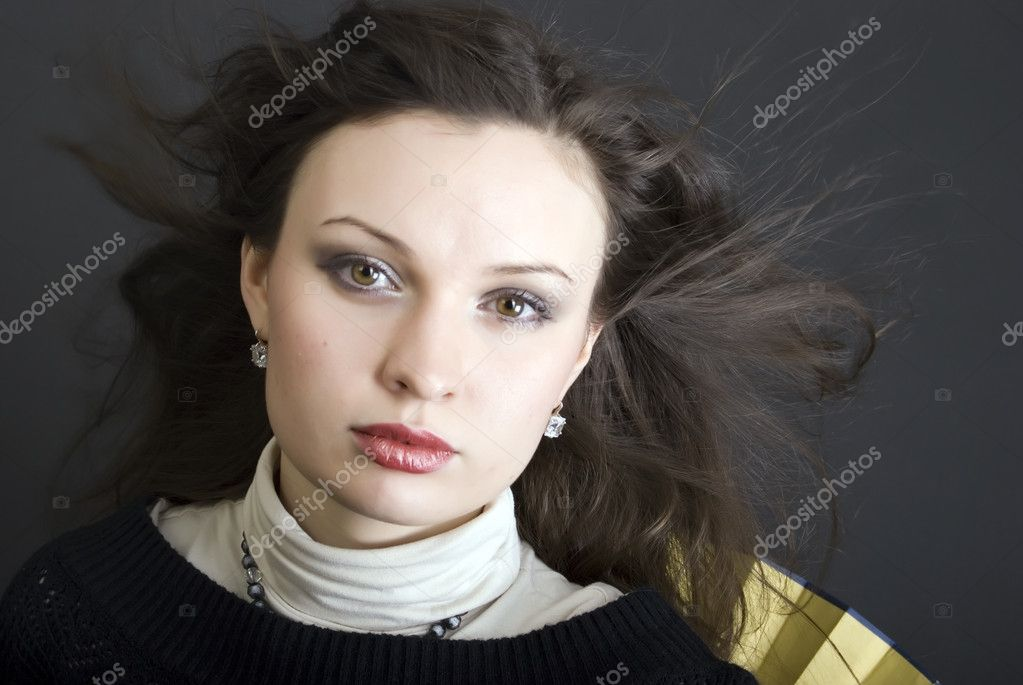 Portrait of a young beautiful brunette with the hair blowing about — Stock Photo #4142743