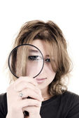 Young girl with magnifying glass — Stock Photo