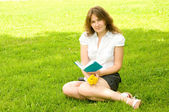 Woman with book on lawn — Stock Photo