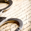 Handcuffs on constitution - Stock Photo