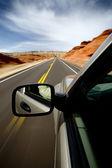 Coche conduciendo a través del cañón de borrego, wyoming, con movimiento borroso. suv, foco en el espejo. — Foto de Stock