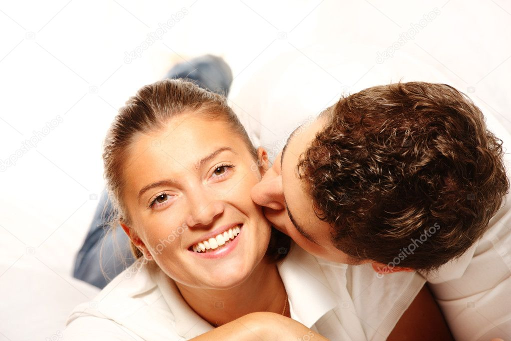 A young nice couple resting on a sofa and kissing over white background — Stock Photo #3912277