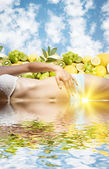 Beautiful female body in water over fruits and sky — Stock Photo