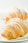 Fresh croissants on white plate with powdered sugar — Stock Photo