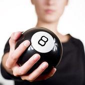 Mujer sosteniendo la bola negra 8 — Foto de Stock