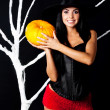 Slender girl dressed as a witch holding a pumpkin at the tree at — Stock Photo