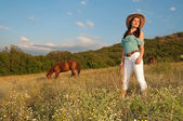 Girl cowboy standing in a field with a horse — Stock Photo