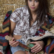 Cowgirl playing the ukelele — Stock Photo