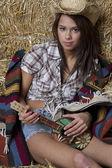 Cowgirl playing the ukelele — Stock Photo