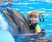 Child and dolphin in blue water.
